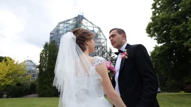 Krásný stylový novomanželský pár pózuje s růžové svatební kytice v botanické zahradě, skleněné konstrukce pozadí