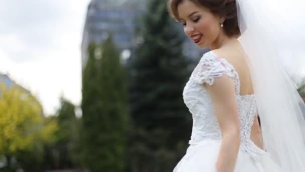 921ca19de5 Encantadora joven morena novia con maquillaje brillante circundar en  vestido blanco y velo
