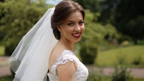 Detailní záběr úsměvem nevěsta na sobě bílé šaty a závoj s světlý make-up taneční venku, zeleného parku na pozadí