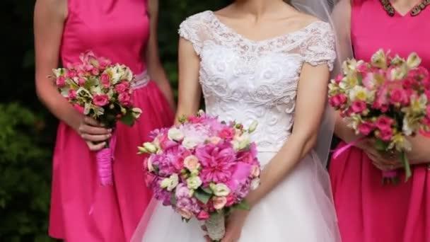 Krásná nevěsta stojí mezi družičky v růžových šatech držení kytice růží