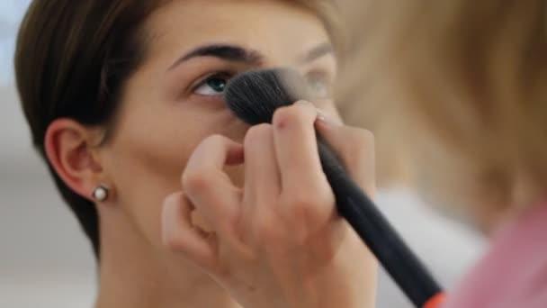 Umělec vyrovnávací pudr s tvoří kartáč na bruneta mladá žena s krátkým účesem
