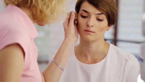 Krásná žena s světlé make-upu očí líčením sexy černá podšívka. Obrazec šipky módy. Krásy make-up s oční linky štětcem na tváři hezká žena