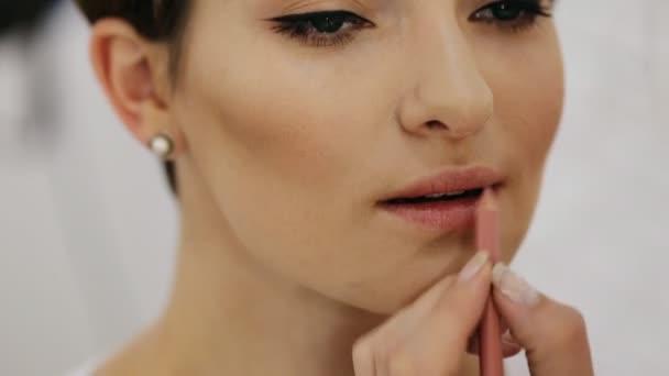 Matita labbra sulle labbra della donna castana attraente in studio cosmetico, salone di bellezza