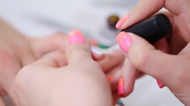 Maniküre im Schönheitssalon. Zeichnung von Ornamenten auf Fingernägeln.