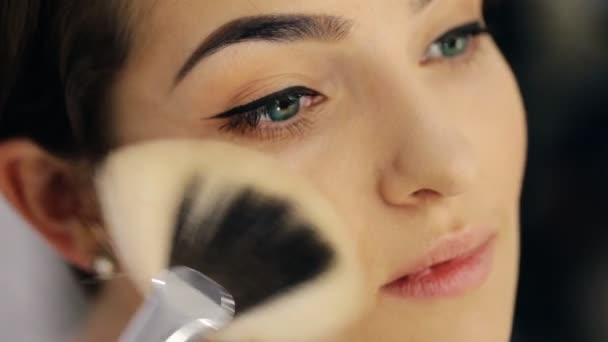 Krásná mladá žena se zelenýma očima a krátký sestřih na zrcadlo použití prášku na tvář