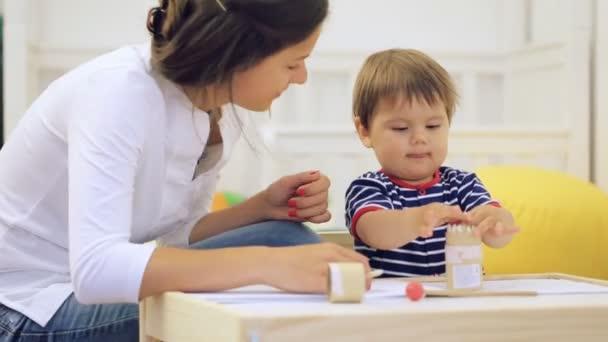 Mladá bruneta mamince hrát se svým malým synem doma