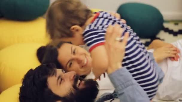 Šťastná rodina tráví společně čas doma, otec líbat jeho syn ležel na posteli