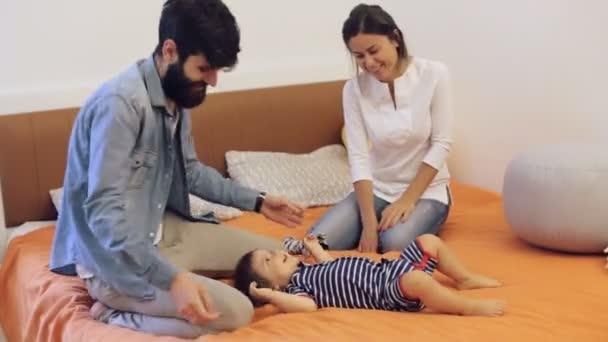 Krásná mladá matka, otec a syn ležel a hrát spolu na posteli
