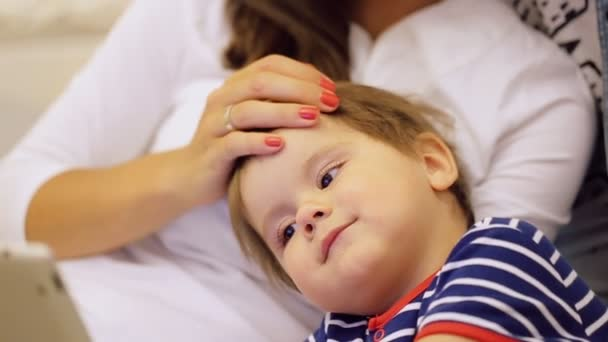 Chiudi-upof giovane madre toccare la testa di suo figlio sveglio utilizzando computer tablet