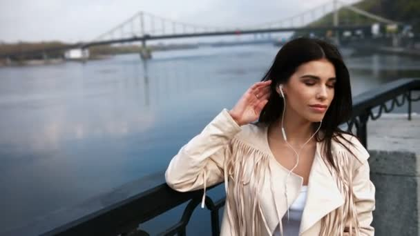 junge Frau steht auf der modernen Brücke, Fluss im Hintergrund, berührt ihre Haare, hört Musik mit Kopfhörern