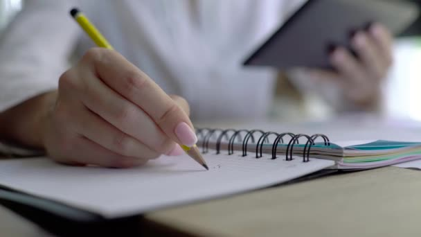 Close-up of female hand holding a pencil and writing some research notes in the appointment book