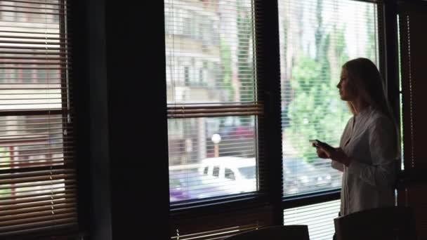 Poloviční délka portrét mladých podnikatelka pohledu na dotykový panel, zatímco postavení v moderních kancelářských prostor interiéru, okouzlující inteligentní žena číst text na digitálním tabletu během rekreace