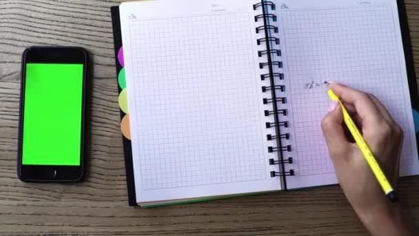 Nő kézzel írt Megjegyzés: notebook irodai íróasztal és szúró telefon-val egy zöld képernyő. Modern élet, digitális háttérrel. Felülnézete