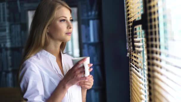 Delicious tea at the morning. Portrait of blond contemplating young pretty lady with white cup looking out the window