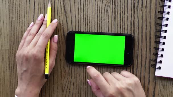 Pohled shora ženské ruky s chytrý telefon, zápisník a tužku dřevěný stůl pozadí