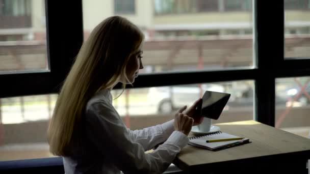 Szép szőke, fehér inget, amelyek a kávé segítségével Tablet PC a kávézóban, oldalnézetből