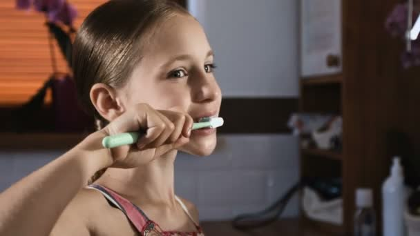 Child girl in pink pyjamas washing and brushing teeth in bathroom