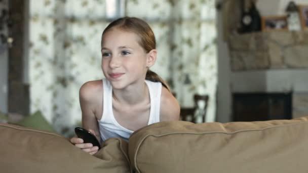 Legrační holčička drží dálkové ovládání usmívá a směje se stojící za gauč