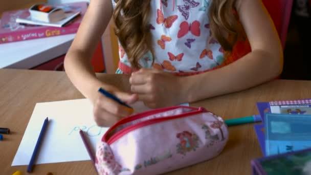 Malé dívky ruku s tužkou je kreslení obrázek na starý dřevěný stůl. pohled shora