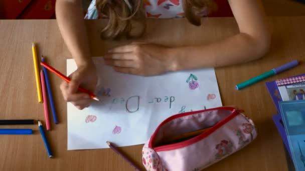 Pohled shora na okouzlující mladá dívka sedí u stolu v dětském pokoji a losování o otci