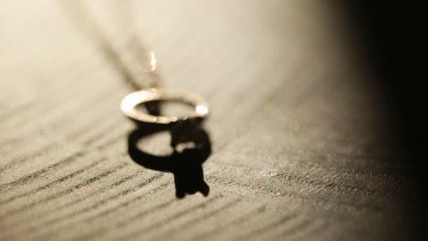Nádherný zásnubní zlatý prsten s drahými kameny a jemným řetízkem, zblízka