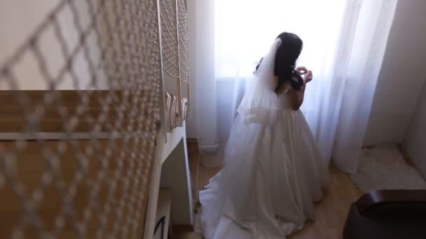 Stilvoller Luxus wunderschöne Brünette Braut posiert neben Fenster auf dem Hintergrund Hotelzimmer. Braut mit Bouquet. Ansicht von oben.