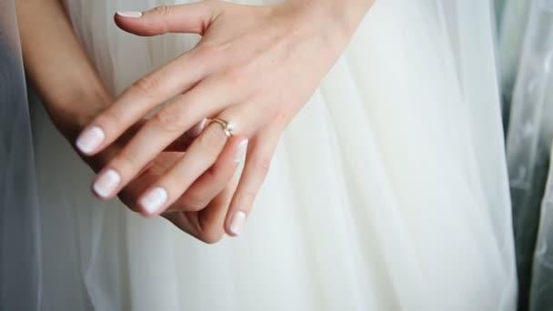 Nevěsta v krásných bílých šatech, ruce snubní prsten s drahokam detail. Ráno nevěsty. Svatební den