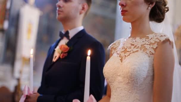 Krásná smyslná blondýna nevěsta v bílým závojem a korunou a pohledný ženich, drží svíčku closeup. Svatební obřad v kostele