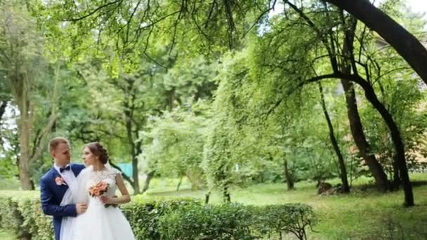 Elegant bride and groom posing together outdoors on a wedding day, embracing holding bouquet in the park