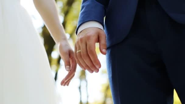Svatební pár, drželi se za ruce s kroužky na pozadí zelené přírody
