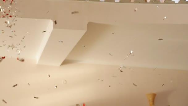Barevné konfety na bílé zdi. Koncepce oslavy a párty