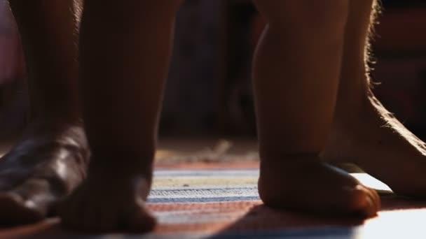 Detail o chlapeček chůzi jeho první kroky s tátou vzadu, na slunné místnosti