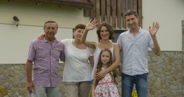 gesto, štěstí, generace, domov a lidé koncept - šťastná rodina, mává rukama před dům venku