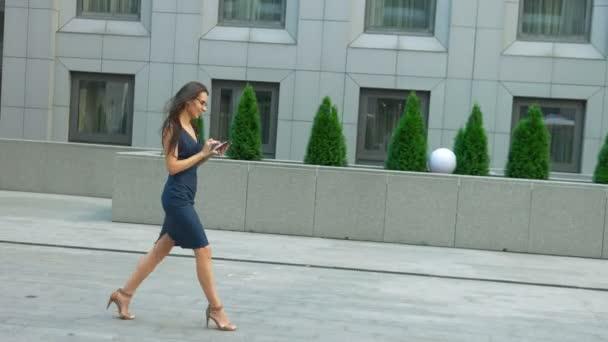 Módní žena pomocí tablet pc chůzi venku. Moderní podnikatelka nosí stylové oblečení a brýle