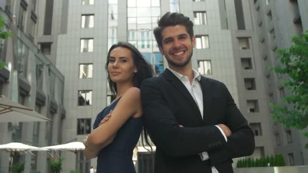 Closeup of confident businessman and businesswoman looking at camera with crossed arms standing outside building