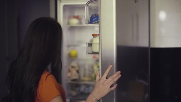 Mladá žena vyndání ovoce z lednice. Zdravé stravování koncepce. Strava. Krásná mladá žena poblíž chladničky se zdravou výživou. Ovoce a zelenina v lednici