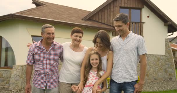 Happy family in three generations with children in summer in front of a house