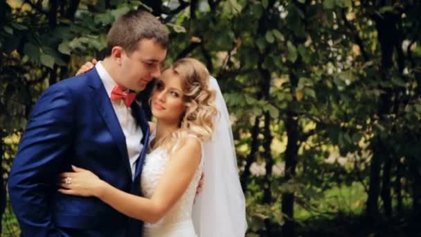 Bride and groom in love looking at each other at beautiful green park shot in slow motion  close up