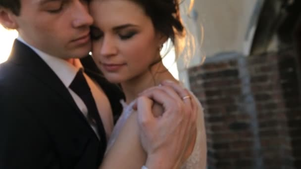 the bride and groom tenderly hugging  at sunset shot in slow motion  close up shot in slow motion  close up