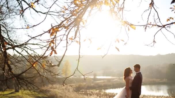 Lovely bride passionately kisses her young handsome groom in park with autumn bright yellow trees shot in slow motion  close up