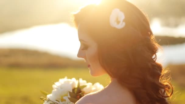 close-up portrait of a beautiful young sexy girl brunette bride with flower  in her hair look attractive in a white dress on a background of autumn forest and leaves posing and smiling shot in slow