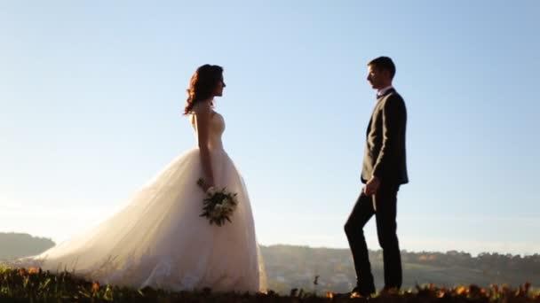 mladý krásný pár nevěsta a ženich jemně objímající a líbání v parku při západu slunce milující pár při západu slunce záběr ve zpomaleném filmu zblízka záběr ve zpomaleném filmu zblízka