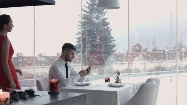 hezký chlap, při pohledu na jeho handwatches a čeká na dívku, mladý muž pomoc svou přítelkyni, aby odpovídala na židli