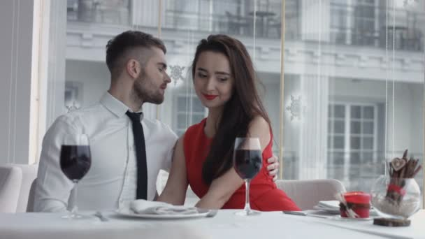 Beautiful young couple with glasses of wine in luxury interior