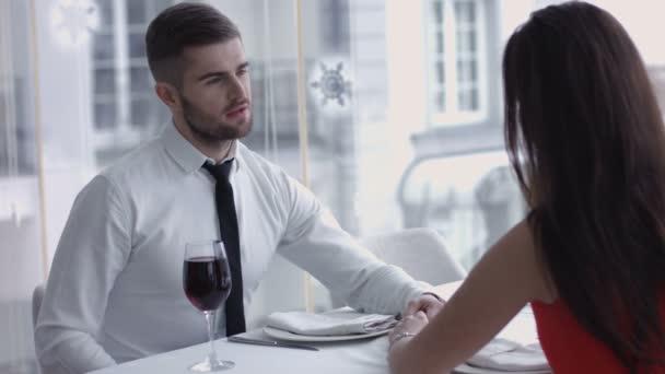 junger Mann stößt mit seiner entzückenden Frau an und trinkt Wein