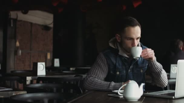 Young man working on laptop inside a cosy half-empty cafe and making a break to sip hot tea.