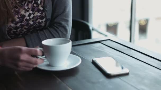 Detail krásná žena v jejím 20s, sedí v kavárně a popíjet nápoje z poháru. Dívka, pít čaj nebo kávu uvnitř