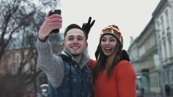 Sladký mladý pár, takže selfie na smartphone. Mužů a žen v jejich 20s s datum venku a fotografování pomocí mobilního zařízení. Lidé dělají tváře na kameru.