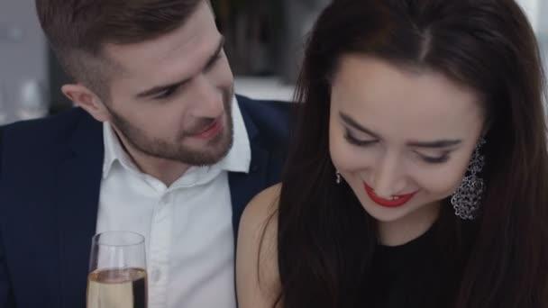 Restaurant, Paar und Urlaubskonzept - lächelndes Paar mit einem Glas Champagner im Restaurant