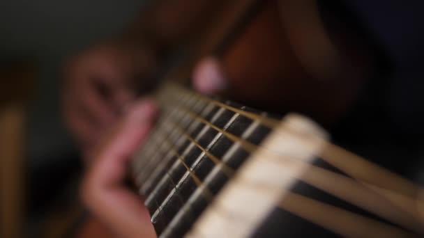 Detailní záběr rukou hrajících na kytaru